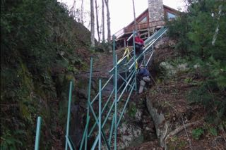 Hill Hiker installers hanging rail on a steep cliff with a hoist system for an incline cliff tram
