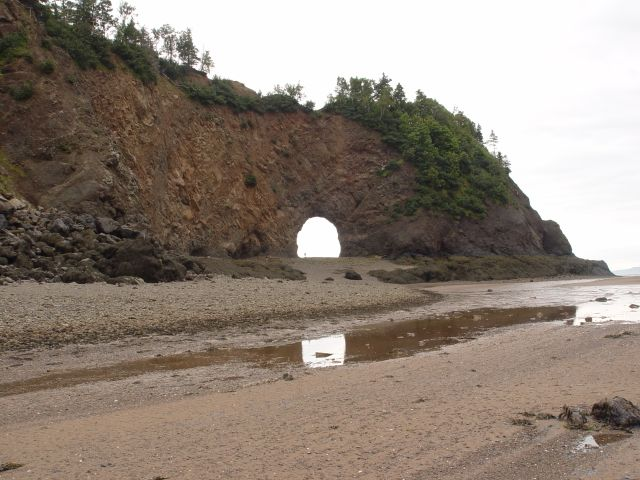 Low tide at Nova Scotia Island project in Canada with natural archway tunnel visible from beach