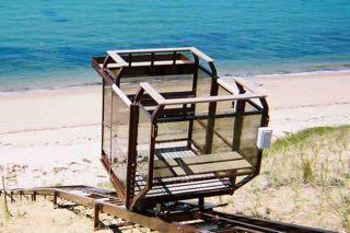 Hill Hiker Beach Elevator Lift / Tram riding down to a sandy beach with blue ocean